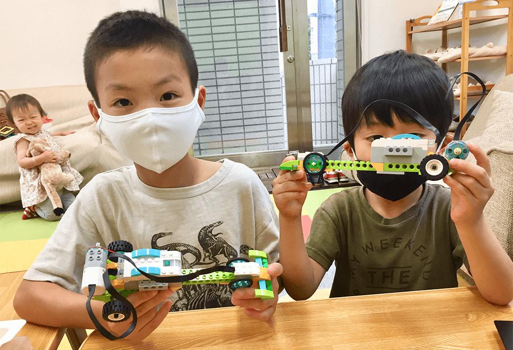 レースカーを見せてくれている2人の小学生の生徒さん