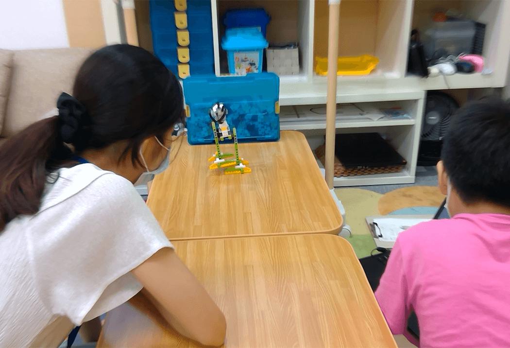先生と一緒にロボットを作っている教室風景